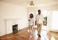 激动的夫妇在移动的天探索新的家 免版税库存图片