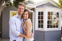 激动的夫妇常设外部新的家画象  免版税库存照片