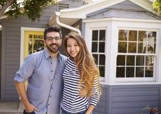 激动的夫妇常设外部新的家画象  免版税库存图片