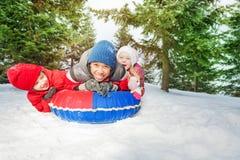 激动的女孩和两个男孩雪管的在冬天 库存照片
