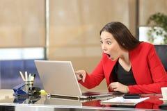 激动的女实业家观看的惊人的新闻 库存照片