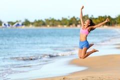 激动的妇女跳跃在海滩的-健身女孩 库存照片