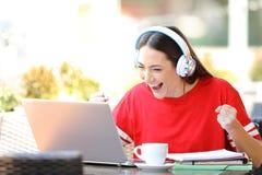 激动的学生电子教学在咖啡馆 库存照片