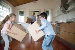 激动的孩子获得带来在箱子给新房的乐趣 图库摄影