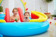 激动的孩子,家庭获得乐趣在露台的五颜六色的可膨胀的水池 库存图片