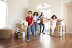 激动的家庭运载的箱子到新的家里在移动的天 库存照片