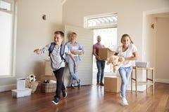 激动的家庭运载的箱子到新的家里在移动的天 免版税库存图片