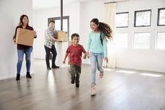 激动的家庭运载的箱子到新的家里在移动的天 图库摄影