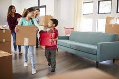 激动的家庭运载的箱子到新的家里在移动的天 库存图片
