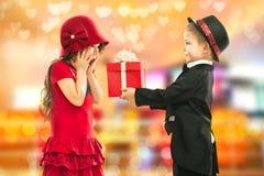 激动的小男孩给女孩礼物的和他的 图库摄影