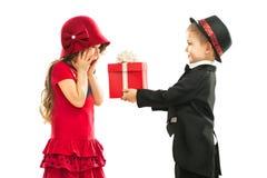 激动的小男孩给女孩礼物的和他的 库存图片