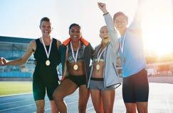 激动的小组有奖牌的赛跑者 免版税库存图片