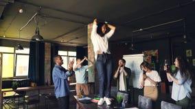 激动的少妇在书桌上跳舞在办公室,当她的同事在桌附近时跳舞,有乐趣和拍手 影视素材