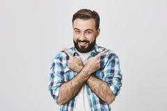激动的年轻成人室内画象与胡子和时髦理发的,指向用与横渡的胳膊的不同的方向 免版税库存照片