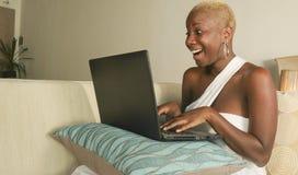 激动的年轻美好和愉快黑美国黑人妇女微笑获得在互联网上的乐趣使用在便携式计算机上的社会媒介 库存图片