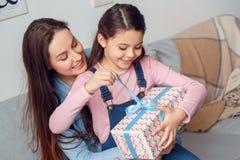 激动的母亲和女儿在家生日坐的女孩打开的当前箱子 免版税库存图片