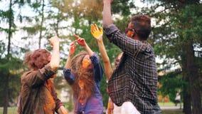 激动的然后笑女孩和的人跳舞在Holi节日和投掷的明亮的油漆获得乐趣户外 股票录像
