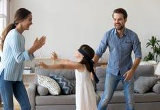 激动的父母获得打与女儿的乐趣滑稽的比赛 免版税库存图片