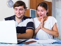 激动的男人和妇女有笔记本的 免版税库存图片