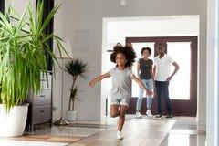 激动的矮小的滑稽的非洲女孩跑的探索的大现代房子在移动的天 免版税库存照片