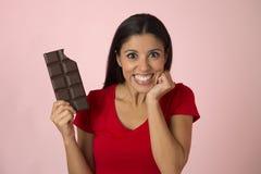 激动的红顶微笑的年轻可爱和愉快的西班牙妇女吃在桃红色背景的巧克力块 图库摄影