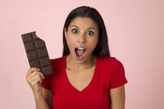 激动的红顶微笑的年轻可爱和愉快的西班牙妇女吃在桃红色背景的巧克力块 库存图片