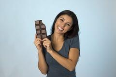 激动的蓝色上面微笑的年轻可爱和愉快的西班牙妇女吃巧克力块背景 图库摄影