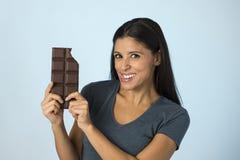 激动的蓝色上面微笑的年轻可爱和愉快的西班牙妇女吃巧克力块背景 免版税库存图片