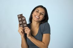 激动的蓝色上面微笑的年轻可爱和愉快的西班牙妇女吃巧克力块背景 库存图片