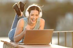 激动的观看在膝上型计算机的女孩佩带的耳机媒介 免版税图库摄影