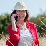 激动的资深妇女谈话在长的草地的电话 免版税库存照片