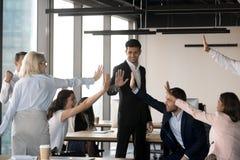 激动的队在办公室给高五庆祝的共有的成功 免版税库存照片