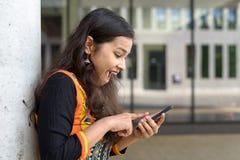 激动的年轻印地安女孩惊叹在sms 免版税库存照片