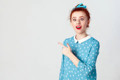 激动的年轻有头发结的红头发人白种人女孩指向她的食指的斜向一边,抬眼眉 库存照片
