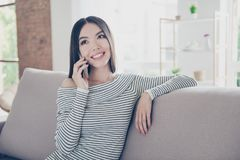 激动美丽亚洲青少年与愉快的微笑在她的pda在家谈话 她穿便衣,坐舒适beig 免版税图库摄影