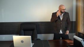 激动跳舞在他的书桌的商人在他的办公室 年轻可爱的英俊的商人滑稽的跳舞在办公室 股票录像