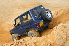 激发在沙子赢取的坑的路drivig 库存照片