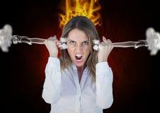 激怒呼喊与在耳朵和火的蒸汽的少妇在头 黑色背景 免版税库存照片