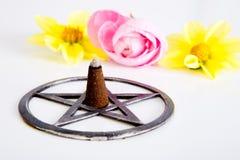 激怒在金属五角星形的燃烧与桃红色和黄色花 图库摄影