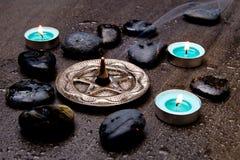 激怒在银色五角星形的燃烧与蓝色蜡烛和黑色 免版税库存图片