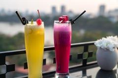 激情与冰的新鲜水果汁在咖啡馆和酒吧的室外桌上 菠萝和红色龙果子 背景的都市湖 图库摄影
