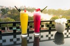 激情与冰的新鲜水果汁在咖啡馆和酒吧的室外桌上 菠萝和红色龙果子 背景的都市湖 免版税图库摄影