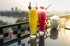 激情与冰的新鲜水果汁在咖啡馆和酒吧的室外桌上 菠萝和红色龙果子 背景的都市湖 库存照片