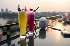 激情与冰的新鲜水果汁在咖啡馆和酒吧的室外桌上 菠萝和红色龙果子 背景的都市湖 免版税库存照片