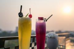 激情与冰的新鲜水果汁在咖啡馆和酒吧的室外桌上 菠萝和红色龙果子 背景的都市湖 免版税库存图片