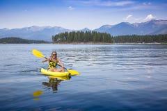 激活,划皮船在一个美丽的Mountain湖的适合的妇女 图库摄影