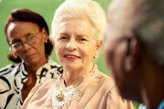 小组年长黑人和白种人妇女谈话在公园 图库摄影