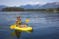 激活,划皮船在一个美丽的Mountain湖的适合的妇女 库存照片