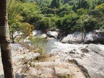 瀑布、树和冰砾在热带森林里 免版税图库摄影