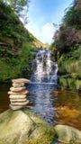 瀑布到与石石标的一个岩石水池里在前景 免版税库存照片